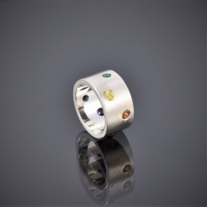 Wide frosted silver band with multi-coloured stones, yellow sapphire showing