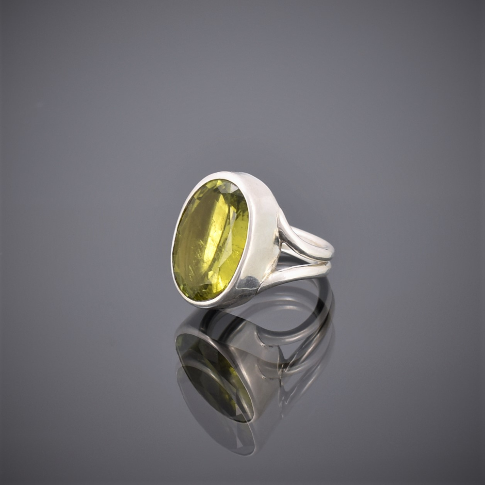Side view of chunky oval peridot and silver wire ring. Peridot set in rubover setting