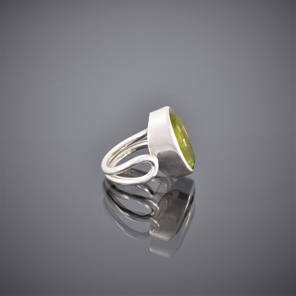 Side view of chunky oval peridot and silver wire ring. Peridot set in rubover setting.