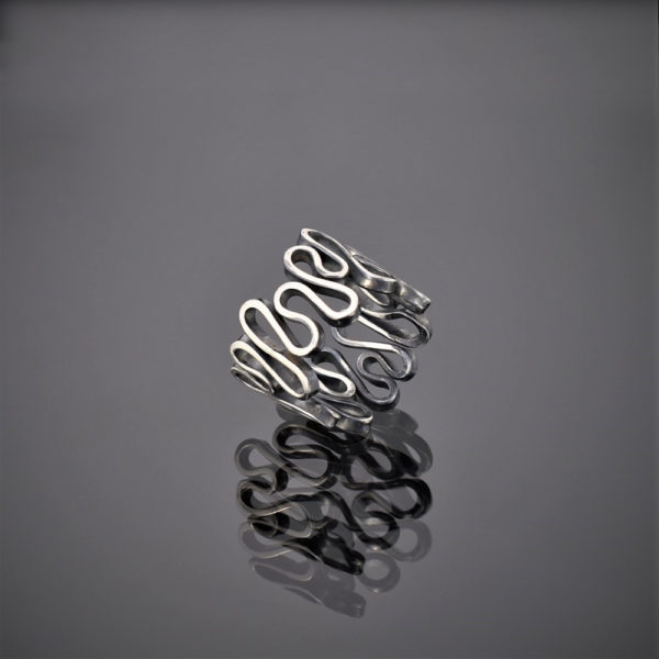 An oxidised silver ring made of one squiggly piece of wire. Left side view..