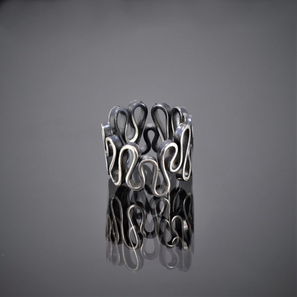 Flat view of an oxidised silver ring made of one squiggly piece of wire.