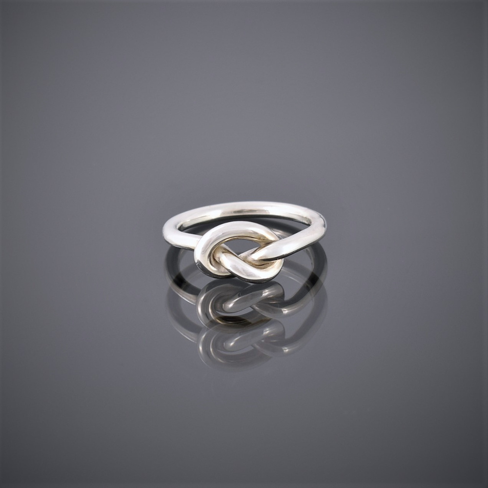 Front view of a solid silver wire ring formed in a knot to represent friendship