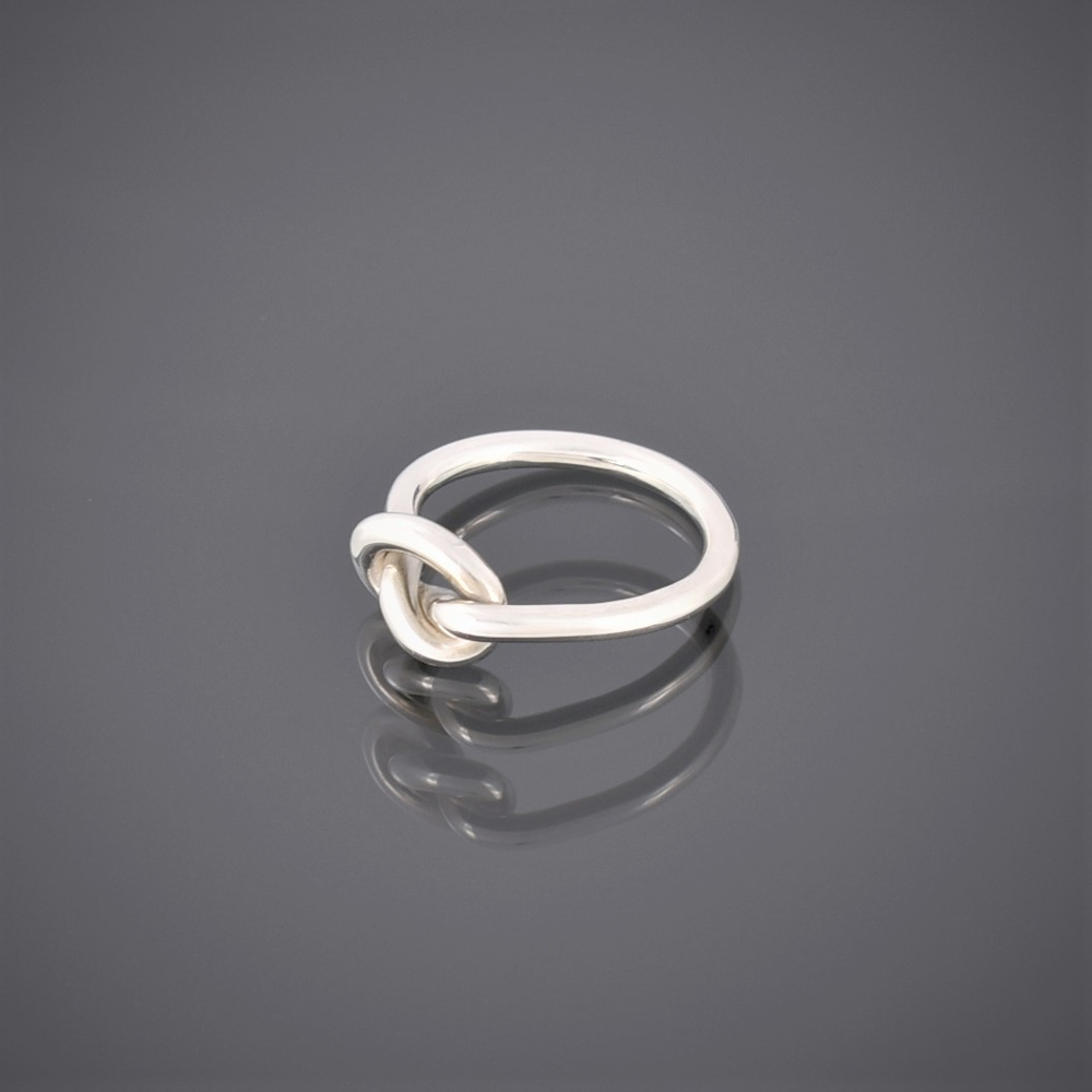Side view of a solid silver wire ring formed in a knot to represent friendship
