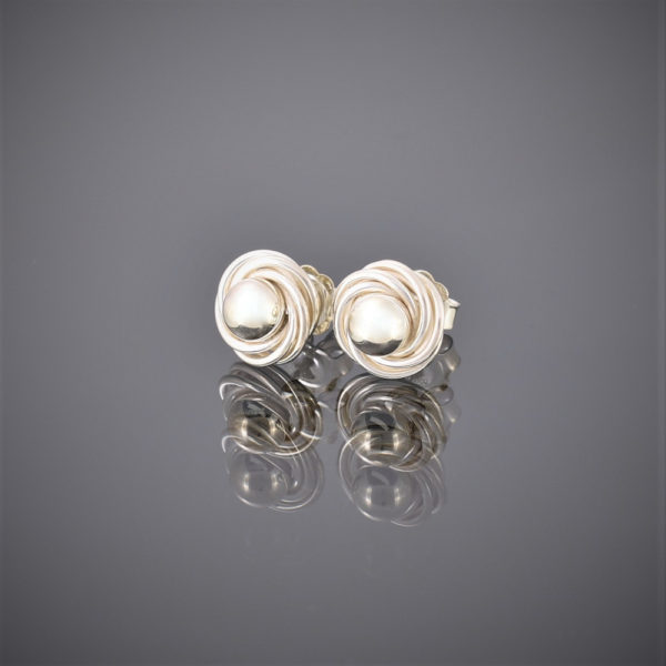Side view of solid silver ball and swirl earrings