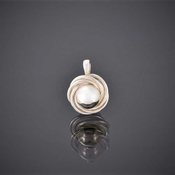 Silver pendant of a solid ball surrounded by silver wire swirl