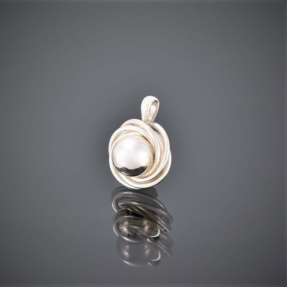 Solid silver pendant of a ball surrounded by silver wire swirls