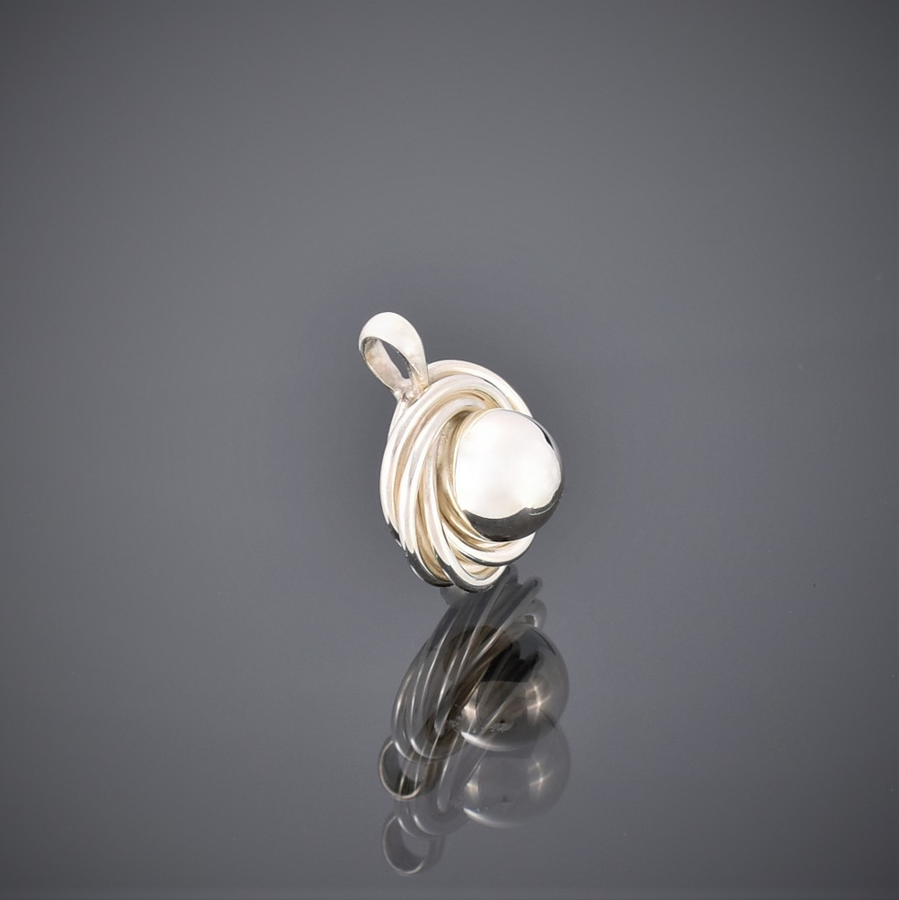 Side view of a solid silver pendant made of a silver ball surrounded by silver wire swirls