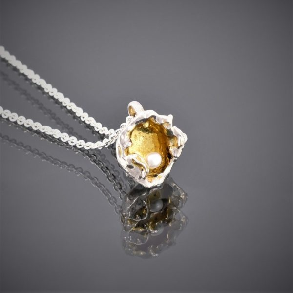 Right view of gold plated water cast silver pendant with freshwater pearl on chain