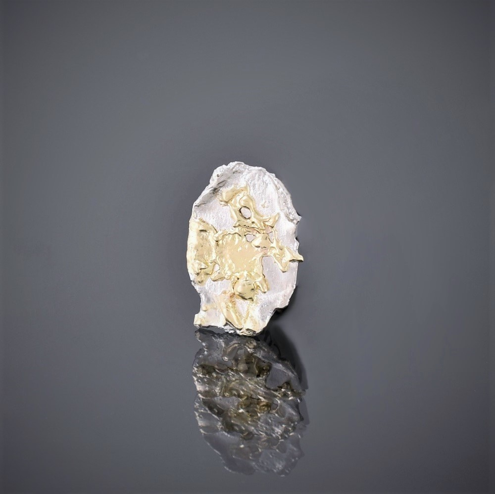 Left view of a solid silver pendant with 18ct gold randomly fused to it. Irregular edging