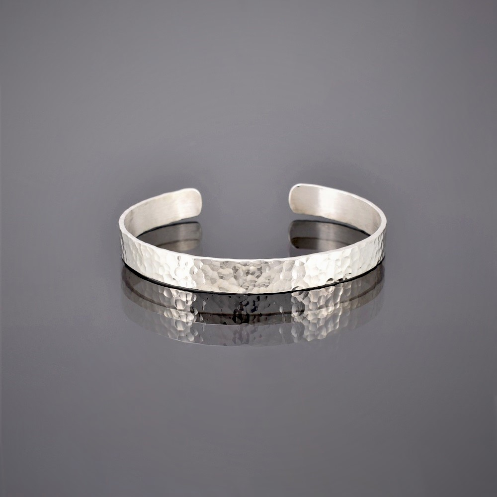 Flat view of a narrow hammered finish solid silver cuff
