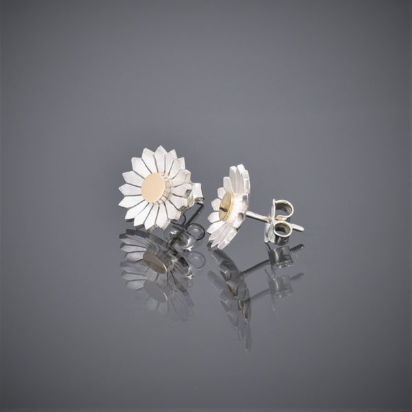 Side view of a pair of brushed silver daisy stud earrings with a solid 18ct gold centre showing butterfly.