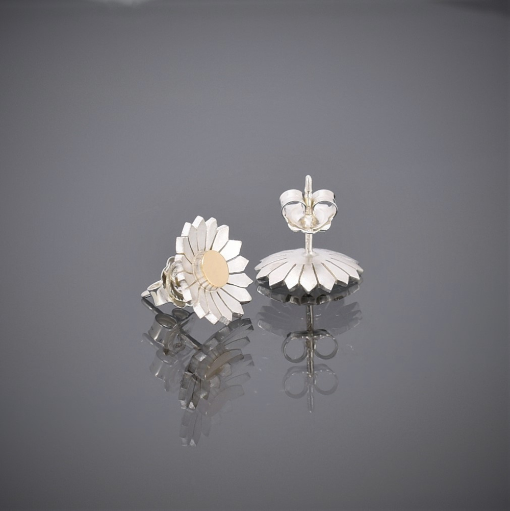 Upright view of a pair of brushed silver daisy stud earrings with a solid 18ct gold centre showing butterfly.