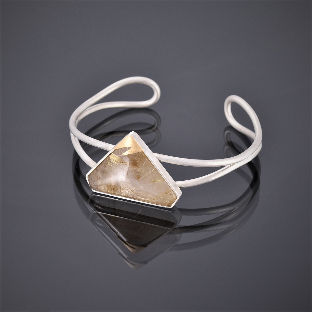 Right side view of a silver wire cuff with triangular rutilated quartz stone and 24ct gold detail