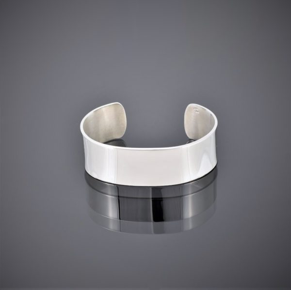 Flat view of a wide solid silver cuff polished to a high shine