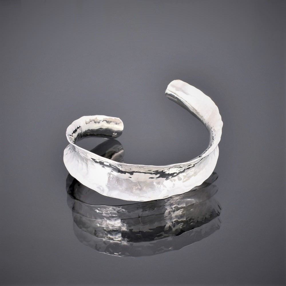 Frton view of an anticlastic hammered silver cuff