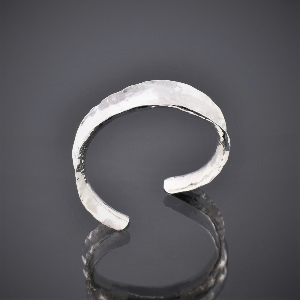 Top view of a hammered silver anticlastic cuff bracelet