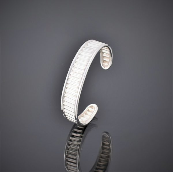 Left view of a narrow corrugated silver cuff with silver wire sides