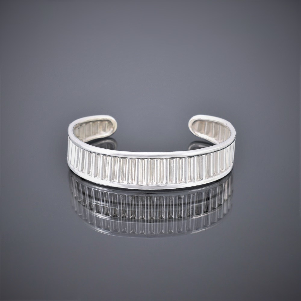 A narrow corrugated silver cuff with silver wire sides