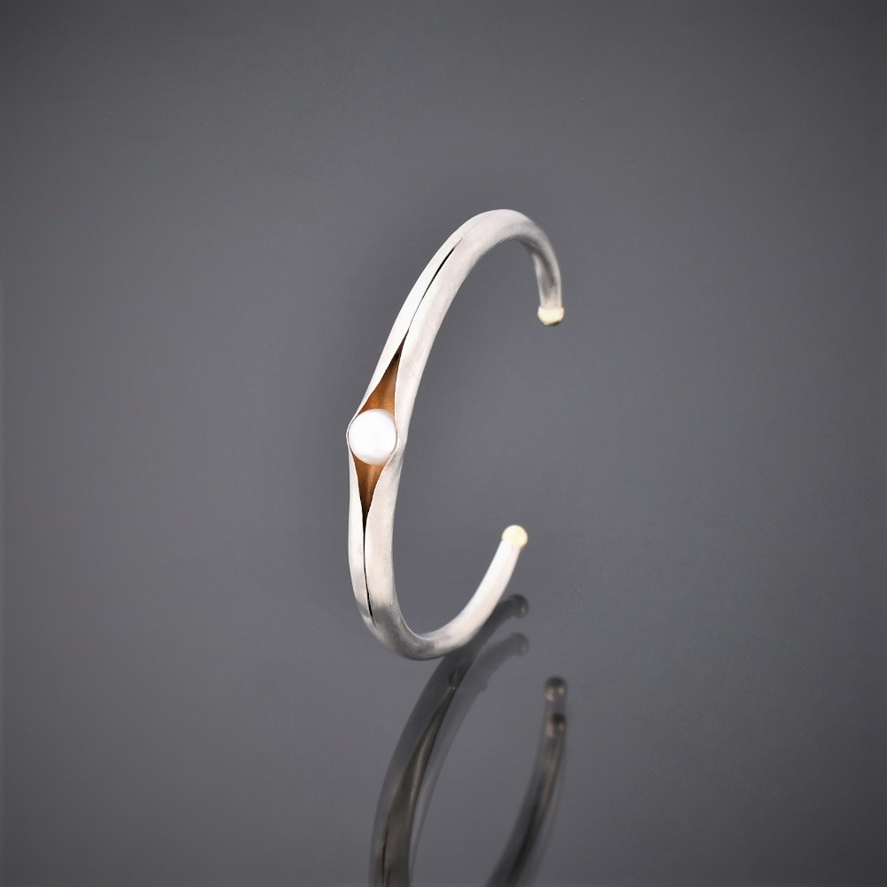 Upright picture of folding anticlastic matt silver cuff holding a freshwater pearl. Gold detailing on tips