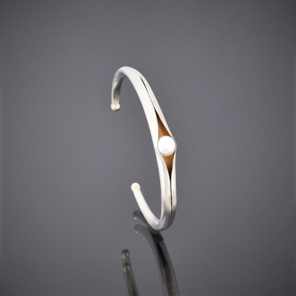 Upright right view of anticlastic matt silver cuff holding a freshwater pearl. Gold detailing on tips