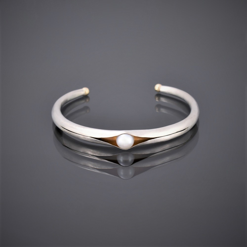 Horizontal view of folding anticlastic matt silver cuff holding a freshwater pearl. Gold detailing on tips