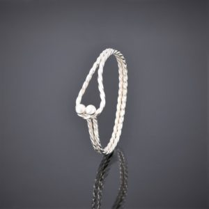 Upright left view of a twisted solid silver square wire bangle with tension clasp