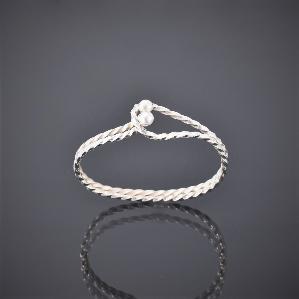 Upright side view of a twisted solid silver square wire bangle with tension clasp