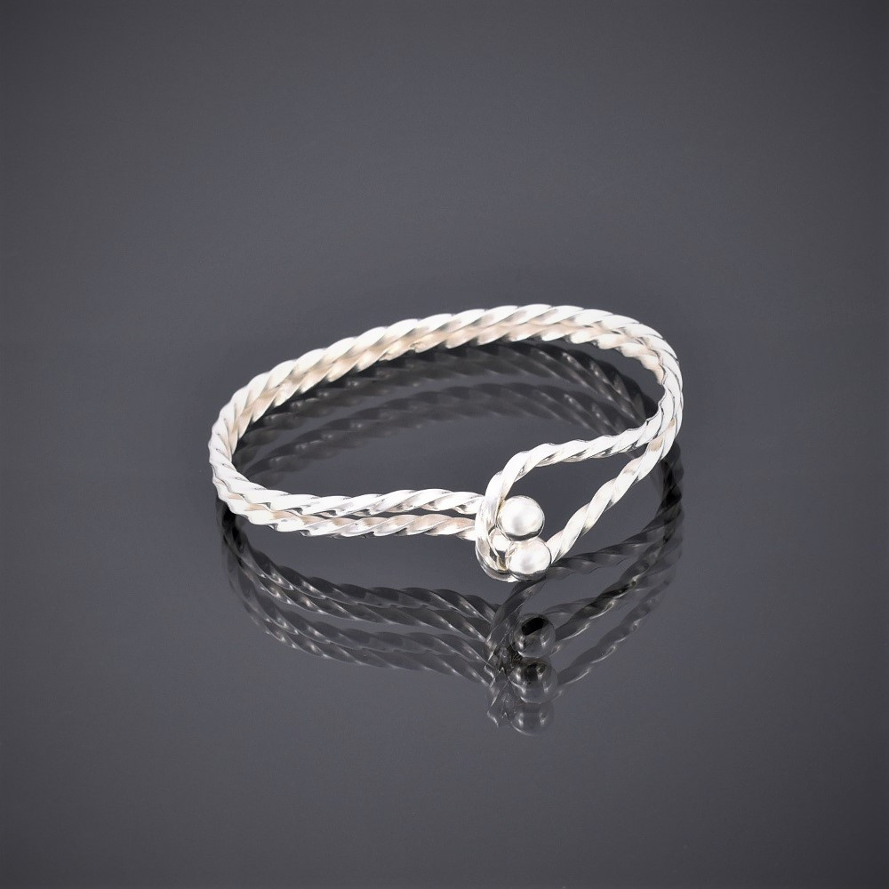 Horizontal view of a twisted solid silver square wire bangle with tension clasp