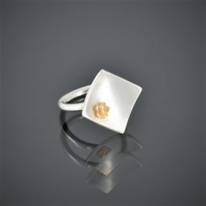right view of a square brushed silver ring with 22ct rose mini flower. Round shank