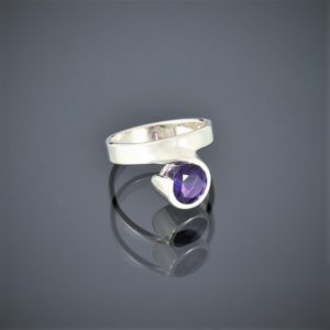 Right view of a wide silver ring with a facetted amethyst set in a rubover setting