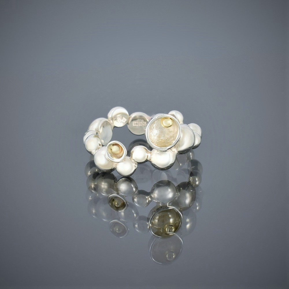 A ring made of solid silver beads of various sizes with gold bead detail