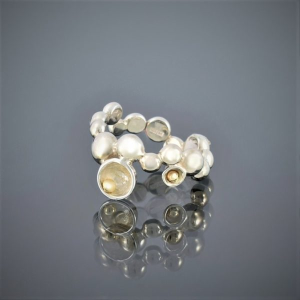 Left horizontal view of a ring made of solid silver beads of various sizes with gold bead detail