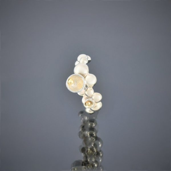 Upright view of a ring made of solid silver beads of various sizes with gold bead detail