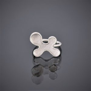 Front view of a silver puzzle piece shaped ring. The ring has a mat finish with round silver wire shank.