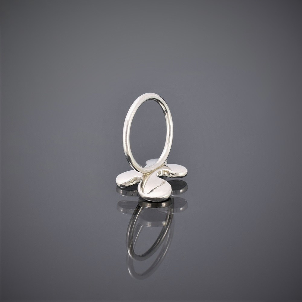 Upside down view of a silver puzzle piece shaped ring. The ring has a mat finish with round silver wire shank.