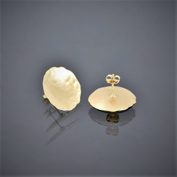 Upside down view of a pair of 18ct yellow gold stud earrings. The gold is thin, slightly concave with a beaten finish